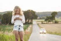 Ragazza adolescente con il telefono cellulare in piedi a lato della strada — Foto stock
