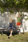 Sister with brother on back yard bench at summer — Stock Photo