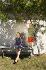 Irmã com irmão no banco de quintal no verão — Fotografia de Stock