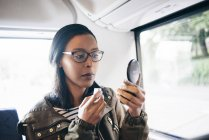 Woman looking in hand mirror while sitting in bus — Stock Photo