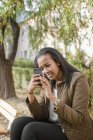 Side view of teenage girl texting in park — Stock Photo