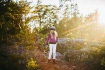 Retrato da garota de pé na floresta, em dia ensolarado — Fotografia de Stock