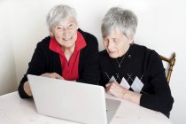 Two senior women using laptop together — Stock Photo