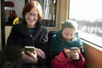 Girl with grandmother sitting in tram and using smart phones — Stock Photo