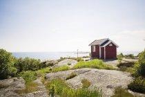 Vue du bâtiment en bois rouge à côté de la mer — Photo de stock