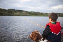 Мальчик рыбачит с собакой, избирательный фокус — стоковое фото