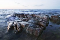 Front view of rocks in sea against sky — стоковое фото