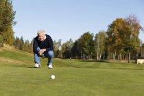 Homme Senior recherche sur boule au terrain de golf — Photo de stock