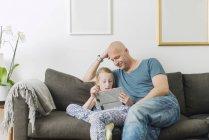 Отец делает домашнюю работу с дочерью дома — стоковое фото