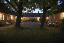 Освещённый задний двор и мотороллер в сумерках — стоковое фото