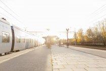 Vue de la plate-forme de la voie ferrée au coucher du soleil, lumière parasite — Photo de stock