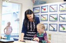 Ragazza con insegnante libro di lettura in classe, concentrarsi sul primo piano — Foto stock