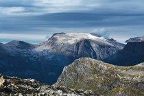 Nevadas montañas rocosas bajo el cielo nublado - foto de stock