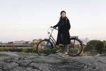 Вид збоку молодої жінки, що стоїть на велосипеді по скелі — стокове фото