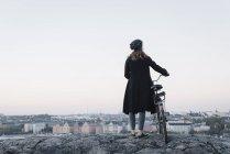 Vista posteriore della giovane donna in piedi in bicicletta sulla roccia — Foto stock