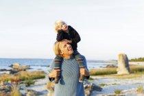 Вид спереди отца на плечи маленький сын — стоковое фото
