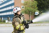 Женщина-пожарный использует пожарный шланг на улице — стоковое фото