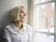 Donna seduta sul davanzale della finestra e guardando attraverso la finestra — Foto stock