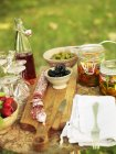 Bottle of syrup and pickled vegetables on table — Stock Photo