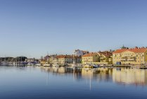 Houses and moored boats with blue sky reflecting in harbor water — Stock Photo
