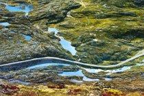 Camino que se extiende a través de Valle de la montaña iluminada de sol - foto de stock