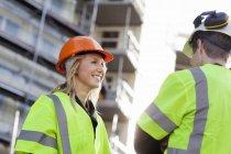Два человека стоят лицом к лицу в защитных шлемах и отражающей одежде на строительной площадке — стоковое фото
