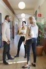 Colegas conversando no corredor, foco em primeiro plano — Fotografia de Stock