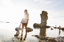 Mother with son standing on rocky beach by sea — Stock Photo