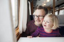 Father and daughter traveling by train and looking through window — Stock Photo