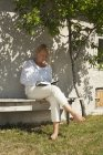 Woman sitting on backyard bench and reading book — Stock Photo