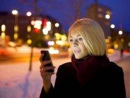 Donna utilizzando smartphone in luci serali — Foto stock