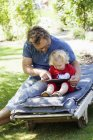 Daughter with father sitting on deckchair and using tablet pc — Stock Photo