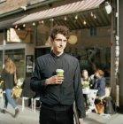 Hombre de pie en la calle con el ordenador portátil y la taza desechable en la mano - foto de stock