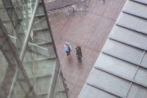 Erhöhte Ansicht von zwei Geschäftsleuten durch Bürogebäude stehen — Stockfoto