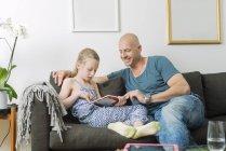 Отец делает домашнее задание с дочерью в гостиной — стоковое фото