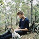Человек, используя ноутбук рядом с собакой в лесу, выборочный фокус — стоковое фото
