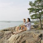 Mid-adult couple sitting on rocks and looking at sea — Stock Photo