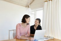 Women looking at each other while using laptop at sitting room — Stock Photo