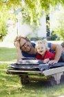 Porträt der Tochter mit Vater auf Liegestuhl liegend und mit TabletPC — Stockfoto