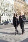 Due donne che camminano per strada, si concentrano sul primo piano — Foto stock