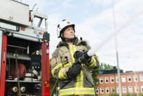Female firefighter using fire hose next to truck — Stock Photo