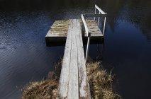 Pequeño embarcadero de madera en el lago bajo la luz solar - foto de stock