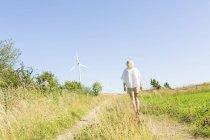 Vue arrière de la femme marchant sur un chemin de terre — Photo de stock