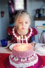 Chica soplando velas en pastel de cumpleaños, enfoque selectivo - foto de stock