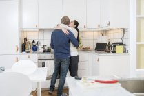 Пара обнимаясь на домашней кухне, дифференциальный фокус — стоковое фото