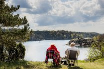 Senior couple sitting on lounge chairs and looking at view — Stock Photo