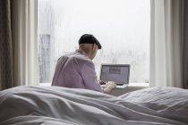 Homme assis sur le lit et à l'aide d'ordinateur portable — Photo de stock