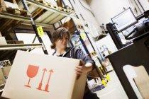 Jeune femme travaillant dans un entrepôt, foyer différentiel — Photo de stock