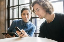 Young people using mobile phone and digital tablet in cafe — Stock Photo