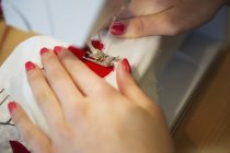 Close up shot of female hands stitching on sewing machine — Stock Photo
